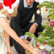 Royalty-Free Stock Photo: Smiling young couple getting gifts at Christmas tree