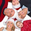Family wearing Christmas hats and lying on floor in a circle - Stock Photo