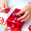 Closeup of a young woman wrapping gift - Stock Photo