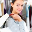 Closeup of a young woman holding bags at a shop - Stockfoto