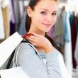 Closeup of a young woman holding bags at a shop - Stock Photo