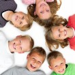 Closeup of young boys and girls lying in a circle - Stock Photo