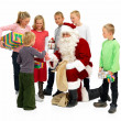 Santa Claus Handing out presents to kids isolated - Stock Photo