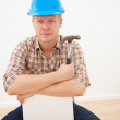 Handyman holding hammer and sitting - copyspace - Stock Photo
