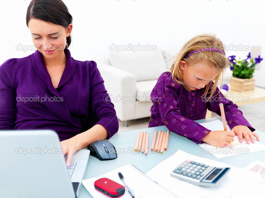 Smiling young woman using laptop with girl drawing — Stock Photo #3270815