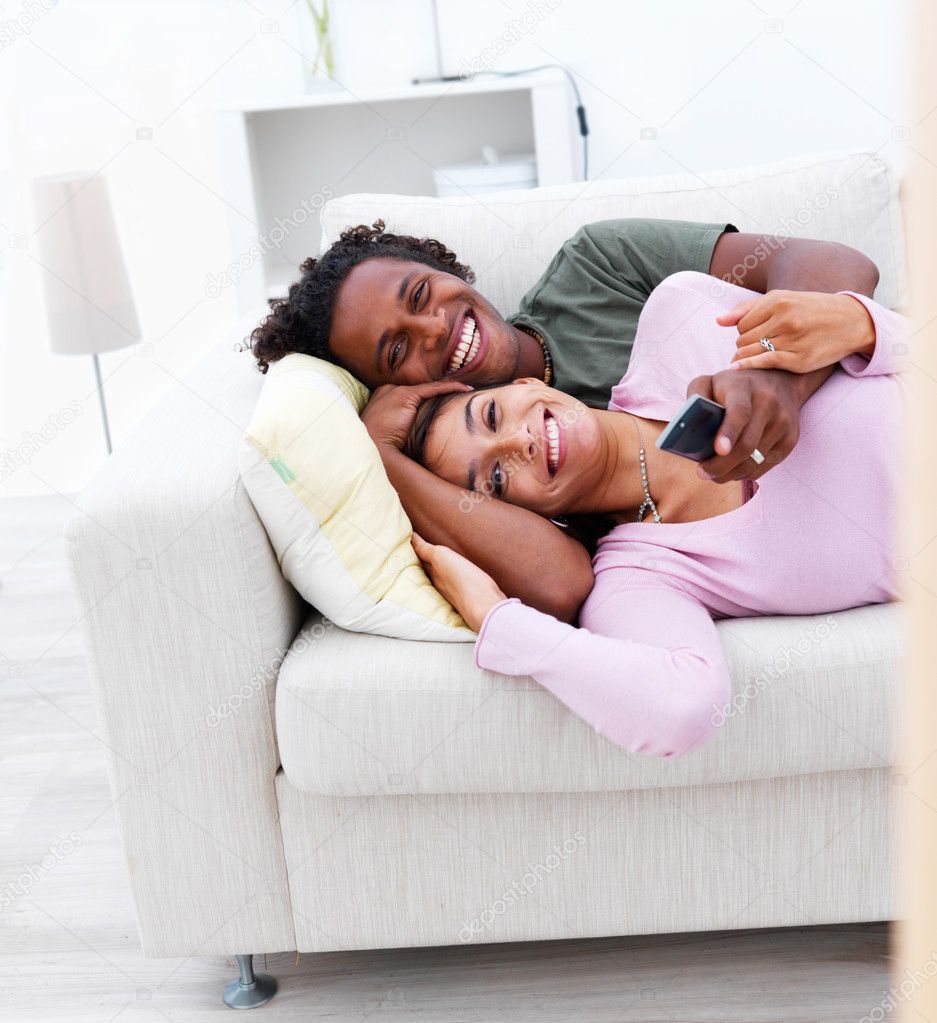 Young couple lying down watching television from the couch in a homely environment — Stock Photo #3272172