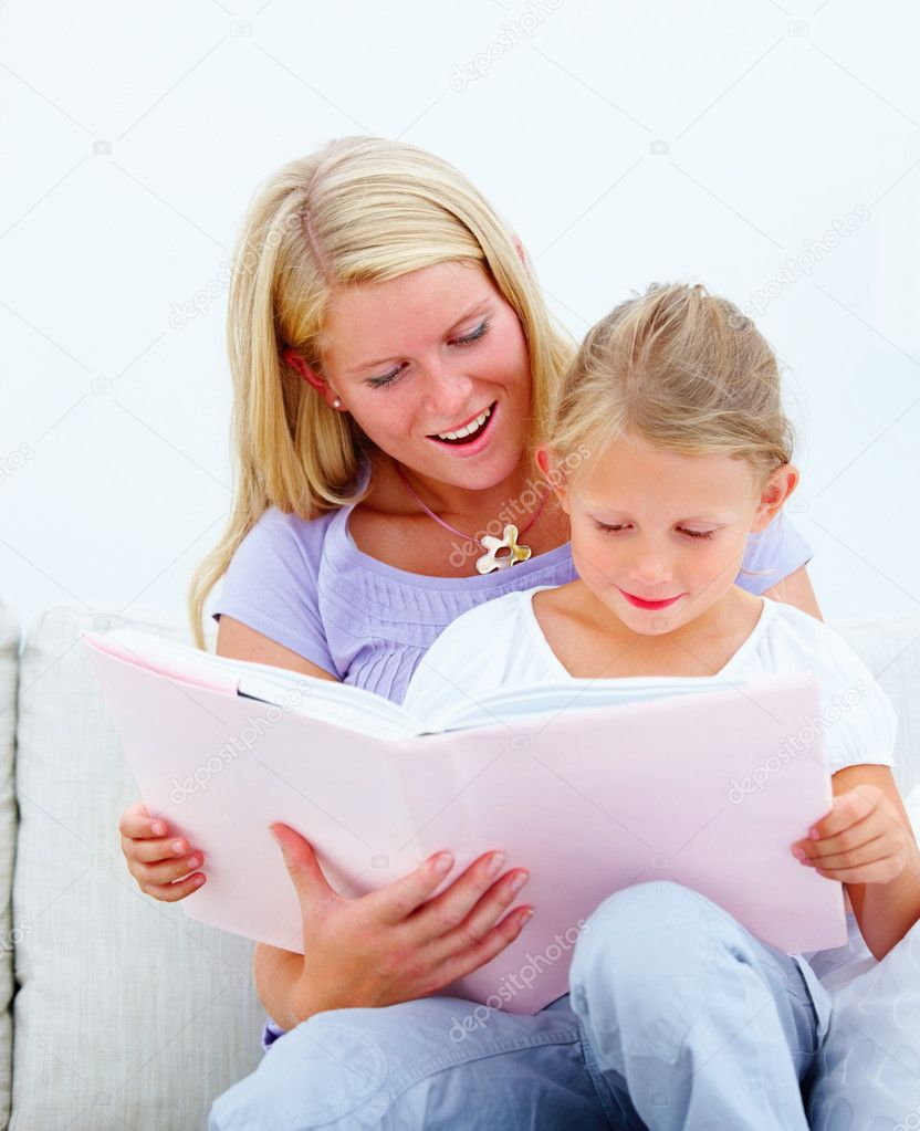 Young mother with her cute daughter reading a book — Lizenzfreies Foto #3273408
