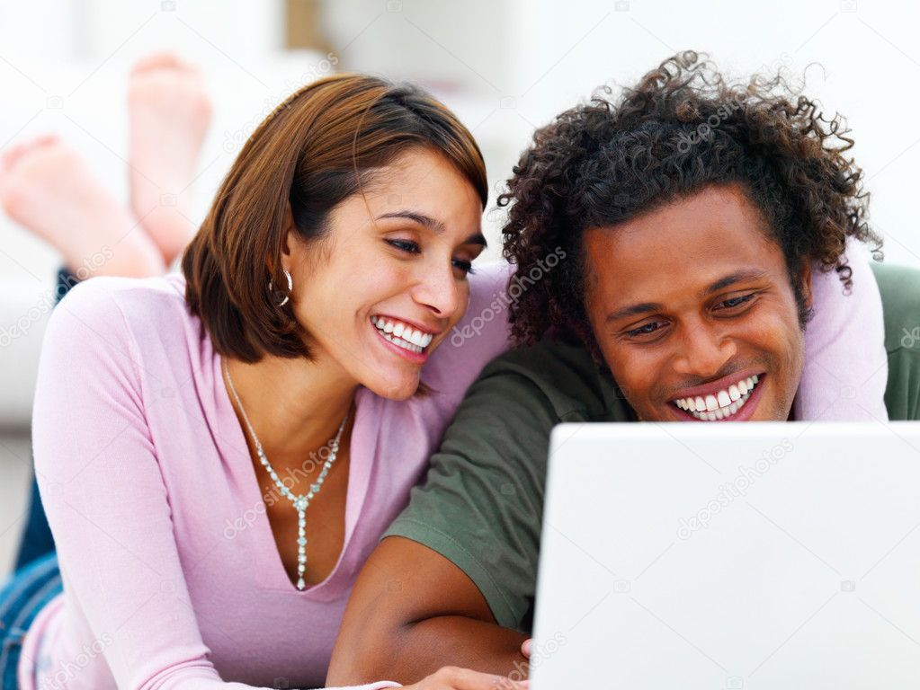 Relaxing young couple looking at a laptop  Stock Photo #3276084