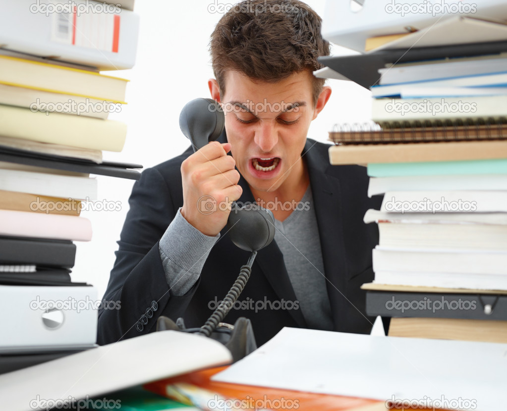 Angry business man shouting over a telephone  Stock Photo #3277309