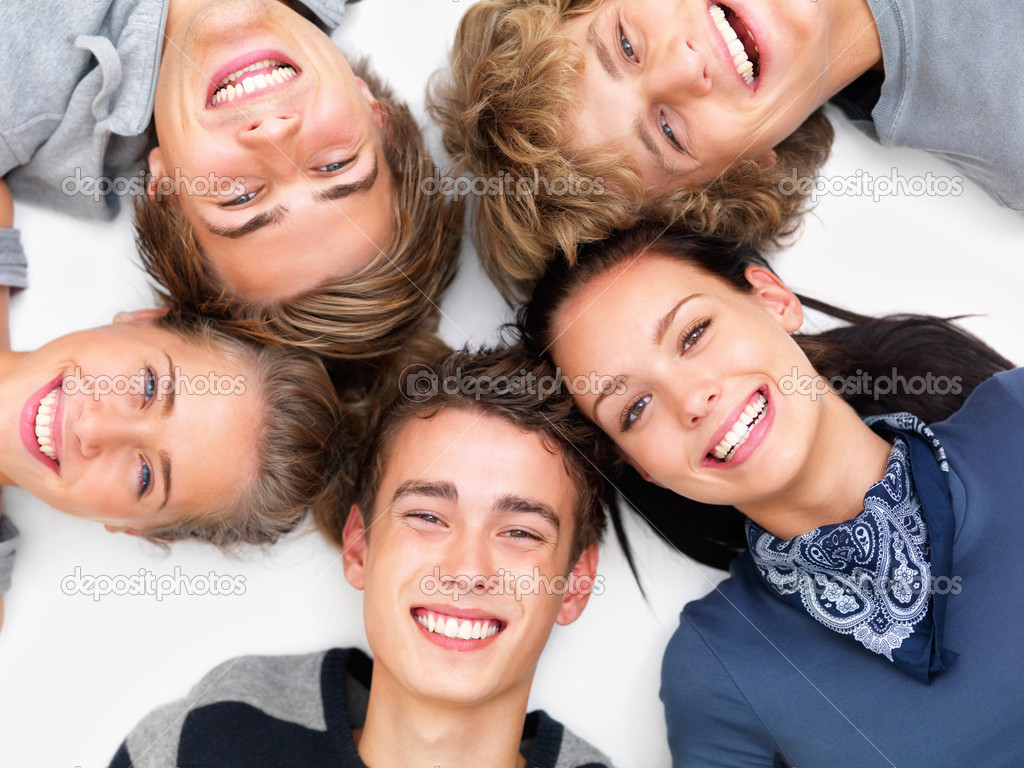 Closeup of happy young friends smiling and lying on white floor — Stock Photo #3277772