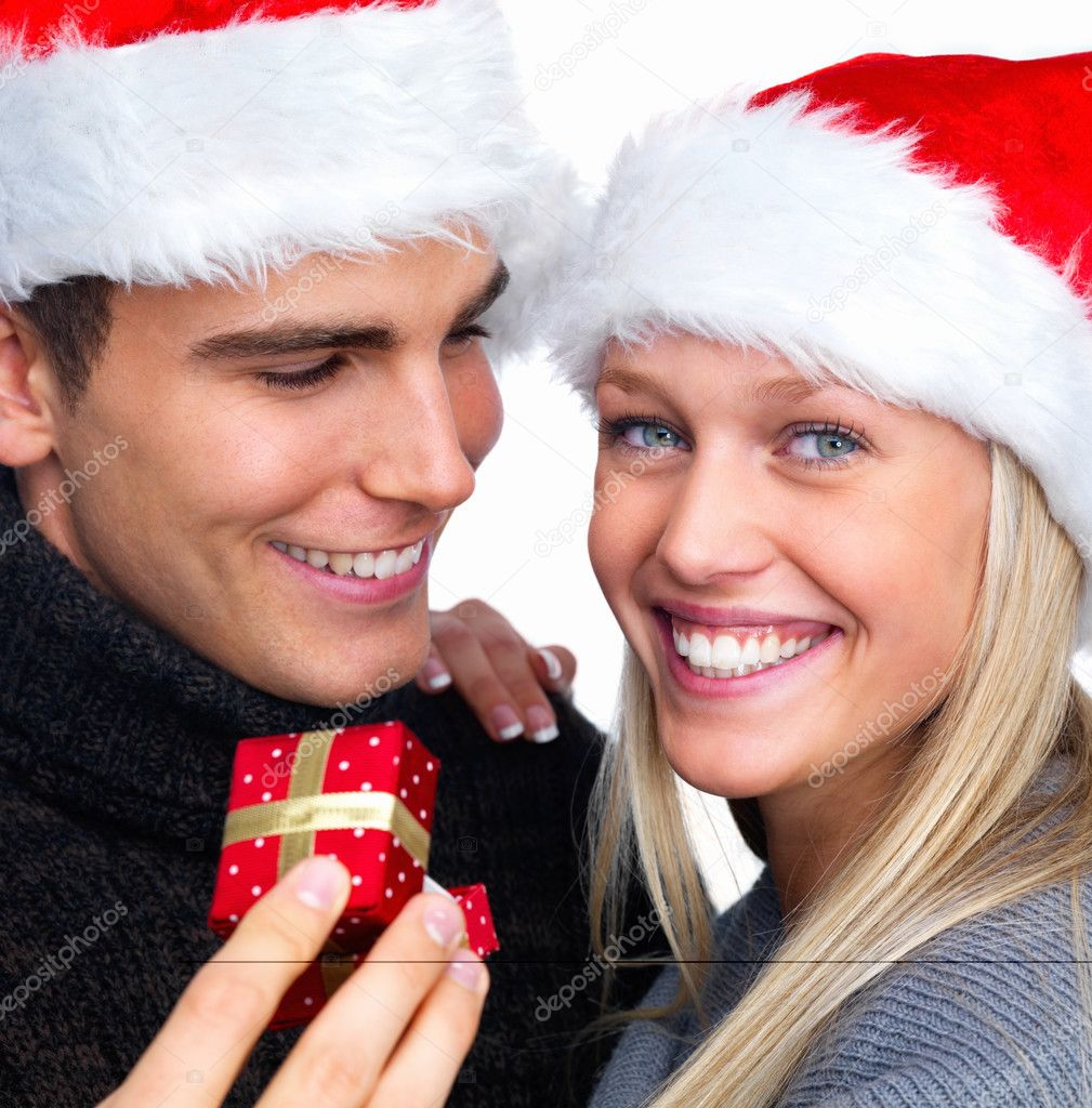 Closeup of a smiling young man giving Christmas gift to a happy girl — Stock Photo #3278426