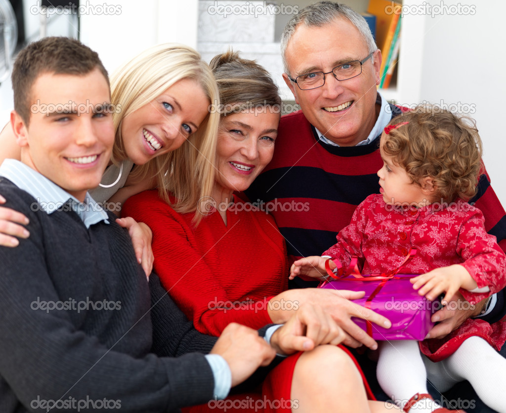 Portrait of a happy family sitting together on sofa at home — Foto Stock #3279146