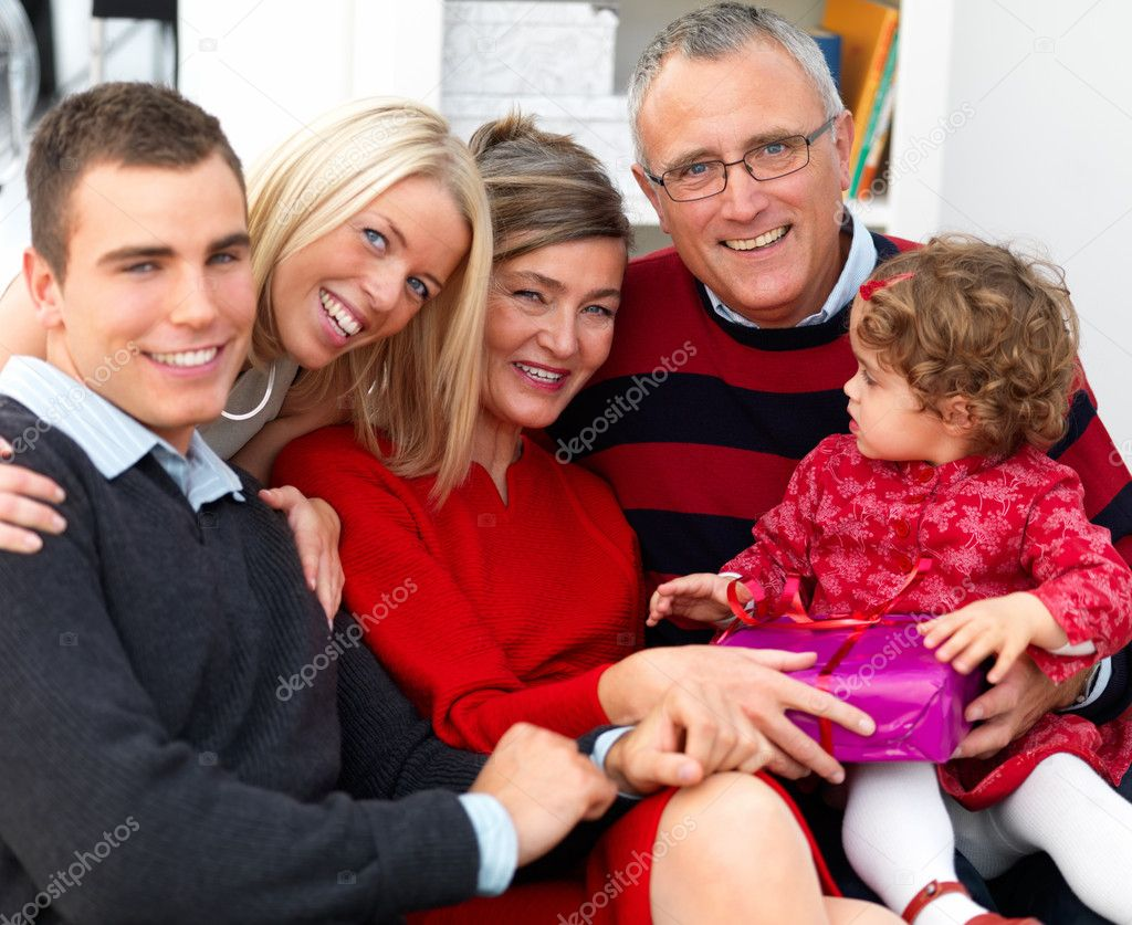 Portrait of a happy family sitting together on sofa at home — Stock Photo #3279146