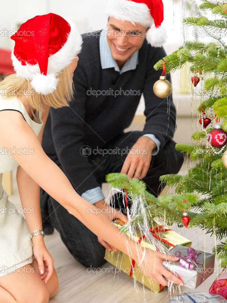 Portrait of a smiling couple holding gifts at Christmas tree — Stock Photo #3279194
