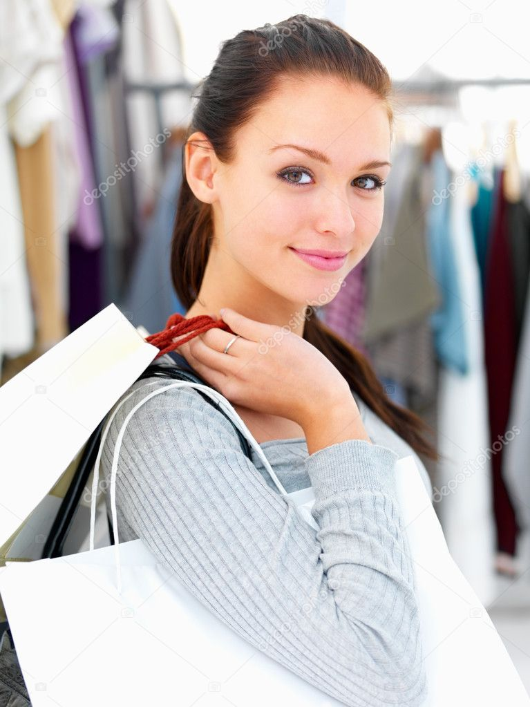 Closeup portrait of a young woman holding bags at a shop — Stock Photo #3279431