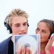 Royalty-Free Stock Photo: Young couple listening to new Cd - copyspace