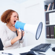 Beautiful business woman shouting into microphone - Stock Photo