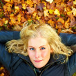 Royalty-Free Stock Photo: Woman lying on fall leaves with copyspace