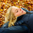 Royalty-Free Stock Photo: Woman lying on fallen leaves with eyes closed