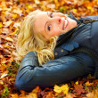 Smiling girl lying on fallen leaves looking at copyspace - Stock Photo
