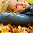 Woman lying on leaves looking at you copyspace - Stock Photo
