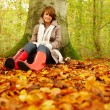 Autumn - Woman sitting under a tree - Stockfoto
