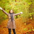 Autumn - Woman playing with leaves in the forest - Stockfoto