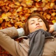 Pretty woman lying down on autumn leaves - Foto de Stock  