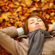 Pretty woman lying down on autumn leaves - Stockfoto