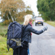 Travel - backpacker girl thumbing a ride - Foto Stock