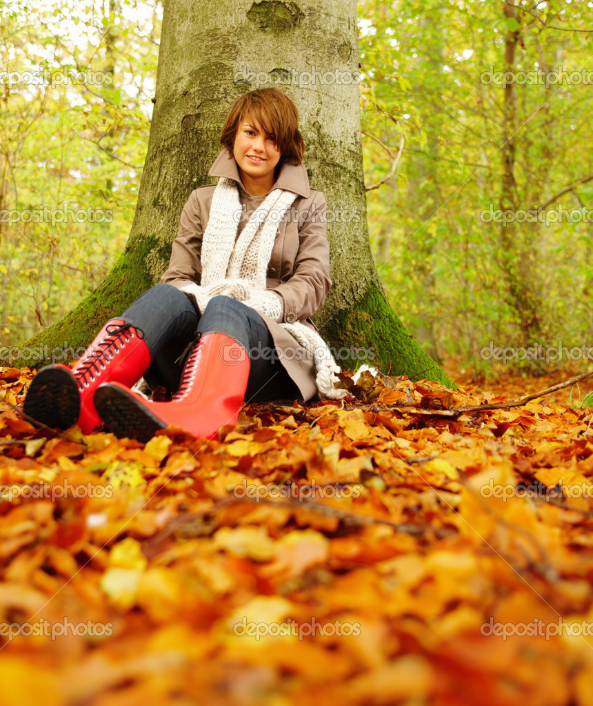 Full length portrait of a beautiful woman sitting under tree in autumn forest — Stock Photo #3289434