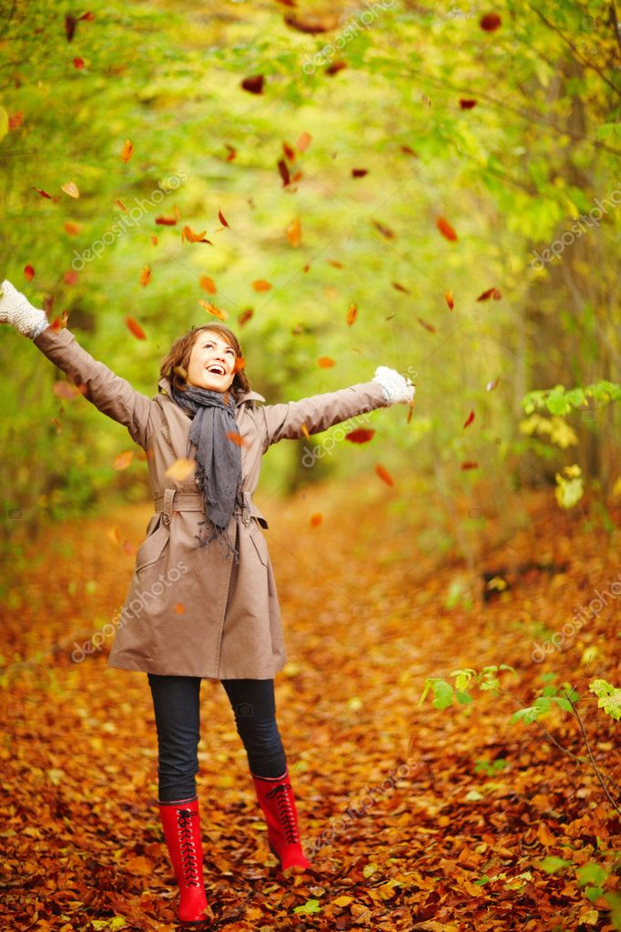 Portrait of a happy woman playing with autumn leaves in forest — Stock Photo #3289455