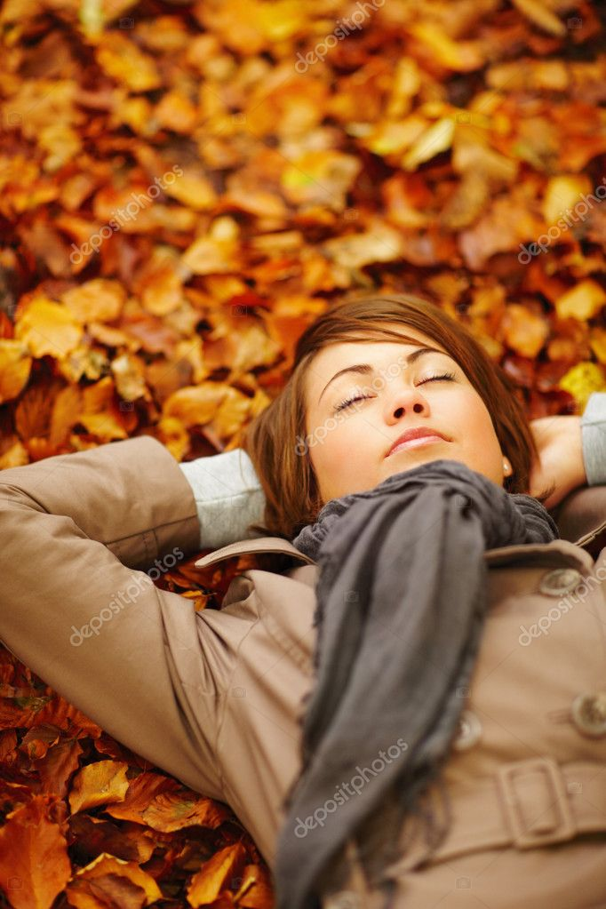 Portrait of a beautiful woman lying on a autumn leaves ground — Stock Photo #3289496