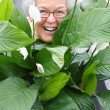 Royalty-Free Stock Photo: Closeup of a happy old woman hiding behind plants and smiling