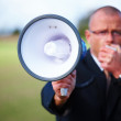 Royalty-Free Stock Photo: Businessman shouting in megaphone about copyspace