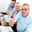 Proud business team giving the thumbs up - Stock Photo