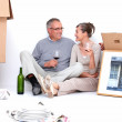 Couple relaxing from moving with glass of wine - Stock Photo