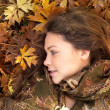 Royalty-Free Stock Photo: Closeup of a beautiful young woman lying on maple leaves