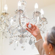 Senior woman looking at a decorative chandelier - Photo