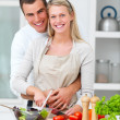 Happy couple  preparing food in the kitchen - Stock Photo