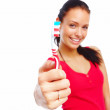 Royalty-Free Stock Photo: Beautiful young woman showing toothbrush and smiling