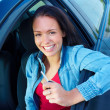 Happy young woman sitting in a car and holding key - Stock Photo
