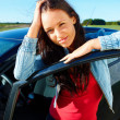 Royalty-Free Stock Photo: Attractive young lady standing outside her car and smiling