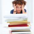 Royalty-Free Stock Photo: Portrait of tired student sitting behind pile of books