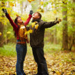 Autumn - Happy couple enjoying falling leaves - Stock Photo
