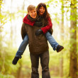Royalty-Free Stock Photo: Mature man giving woman a piggy back in forest