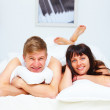 Royalty-Free Stock Photo: Happy couple lying on bed and smiling