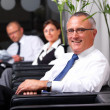 Royalty-Free Stock Photo: Business man sitting on a chair with colleagues in background