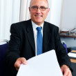 Senior business man in office holding paper in hand - Stock Photo