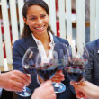 Young businesswoman toasting wine with colleagues - Stock Photo